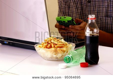Bottles of softdrinks or soda, chips and man working on a laptop computer in the background
