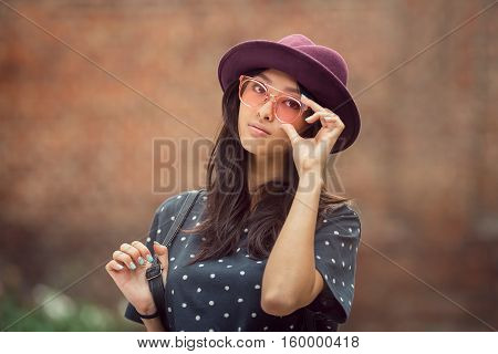 Asian student girl portrait. Beautiful woman holding glasses against brick wall bokeh background. Mixed race student girl in university college campus park serious looking at camera.