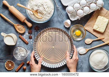 The process of making tart pie dough by hand. Baking cake in kitchen - dough recipe ingredients eggs, flour, milk, butter, sugar on table. Top view. Flat lay.