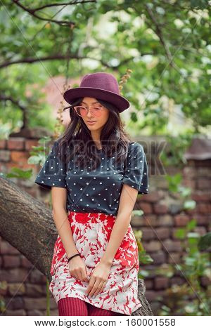 Asian student girl back to school university. Beautiful woman sitting on tree in park against brick wall background. Mixed race student girl on university college campus park serious or sad looking down.