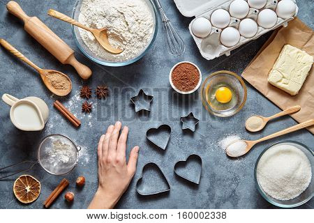 The process of making ginger cookies heart on Valentine's Day. Woman's hand ready to knead the preparing ginger cake. Baking ingredients for homemade pastry on dark background. Top view.