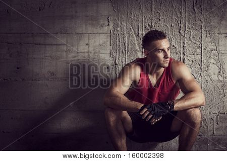 Muscular young athletic built sportsman crouching next to a concrete wall of an abandoned building taking a break from hard workout