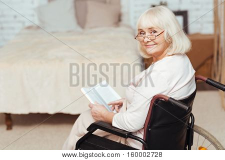 Source of wisdom. Delighted kind elderly woman sitting in the wheelchair and reading book while relaxing at home