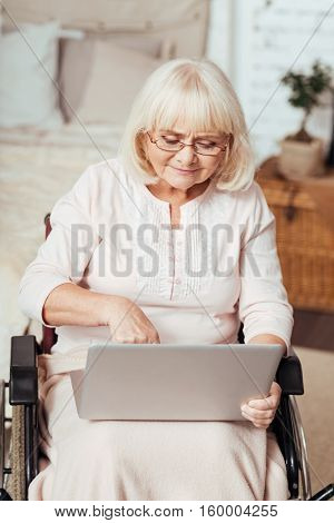Time of progress. Pleasant delighted elderlly woman in the wheelchair using laptop and surfing the Internet