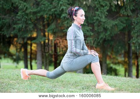 fitness woman stretches during training workout outdoor