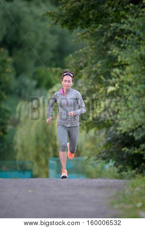 Running athlete woman. Female runner sprinting during outdoors training for marathon run. Athletic fit young sport fitness model in full body length on road outside in nature.