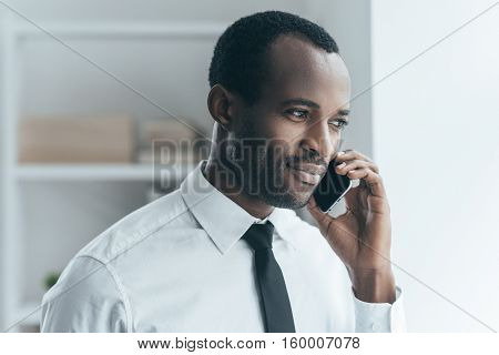 Good business talk. Handsome young African man in formalwear talking on the phone and smiling while standing in creative office