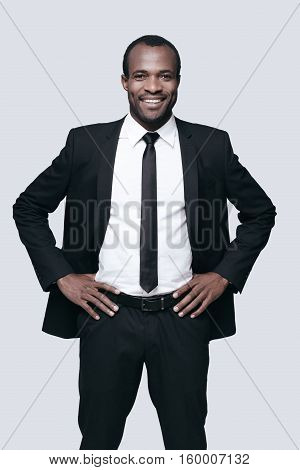 Young and successful. Handsome young African man in formalwear keeping hands on hip and looking at camera while standing against grey background
