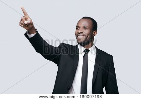 Look over there! Handsome young African man in formalwear pointing away and smiling while standing against grey background