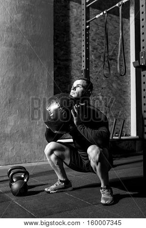 Being in a gym. Persistent confident nice man squatting and holding a medicine ball while preparing to throw it