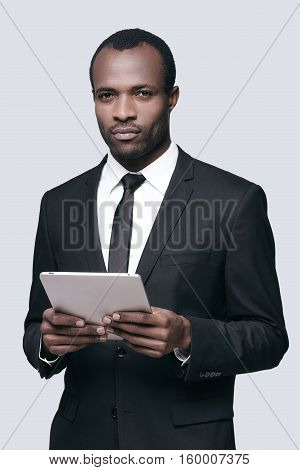 Confident and handsome. Young African man in formalwear working on digital tablet while standing against grey background