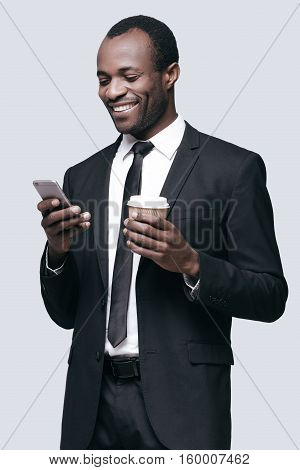 Receiving pleasant messages! Handsome young African man looking at mobile phone and smiling while standing against grey background