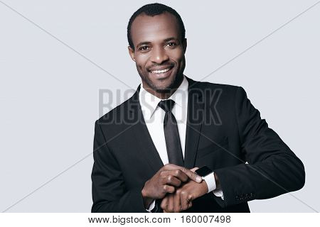 Time is money! Handsome African man looking at camera and smiling while standing against grey background