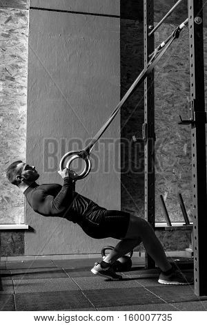 Involved in exercising. Attractive well built good looking man holding gymnastic ring and leaning backwards while doing resistance training exercises