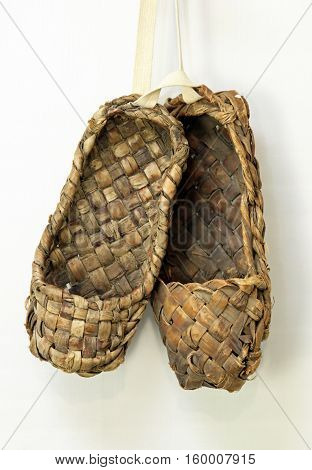 old Russian bast shoes of bark hanging on the wall