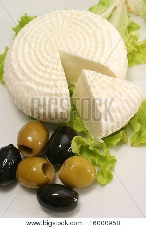 white goat cheese and olives on white dish