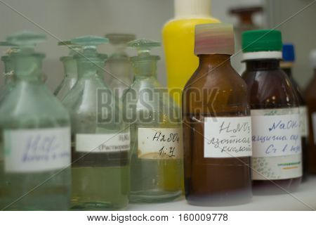 Bottles with the reagents are in a chemistry lab