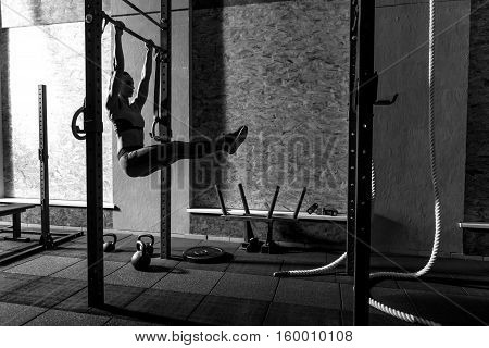 High above the ground. Nice slender woman holding on the horizontal bar and holding legs in front of her while exercising on it