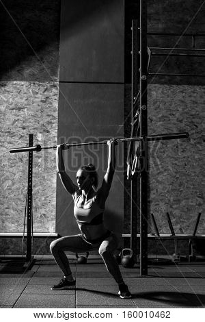 Squatting exercises. Athletic sporty nice woman holding a long metal bar above her head and squatting while concentrating on her weightlifting training
