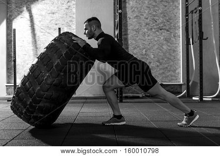 Tire training. Strong handsome bearded man standing and pushing a huge tire while trying to flip it