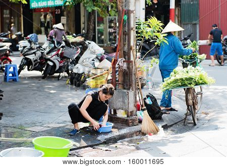 Vietnam, Hue - October 21, 2016: Vietnamese woman washing dishes on the roadside in Hue, Vietnam
