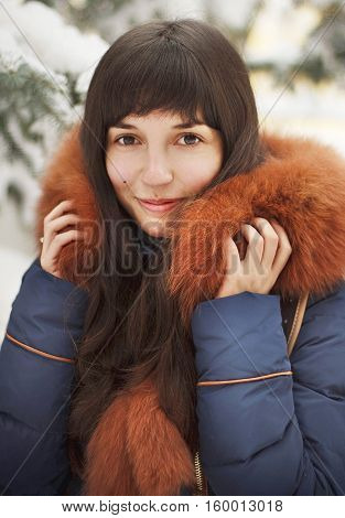 The girl in a fur hood in a winter forest. Brown-haired girl with long hair. Winter portrait of a woman. Sweet and sincere smile