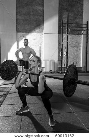 Weightlifting training. Young concentrated athletic woman squatting and holding a barbell while exercising in front of a strong muscular man