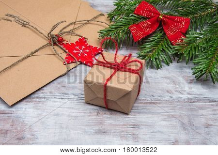 Christmas Gift Closeup On Background Of Spruce Branches And Envelopes