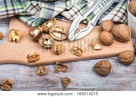 Walnuts, Nutcracker And Checkered Towel On Cutting Board