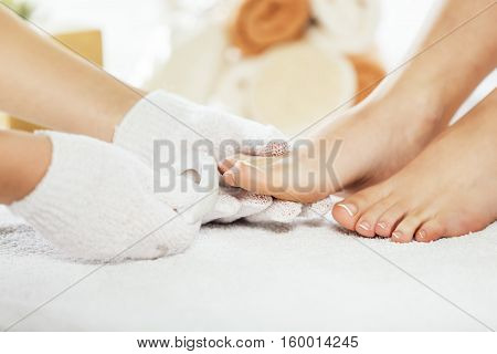 Foot care treatment in spa. Young woman enjoying spa.