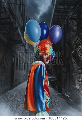 Clown with a bunch of balloons standing in alley.