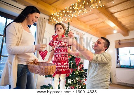 Beautiful young family with little girl decorating Christmas tree at home. Father giving daughter Christmas ornaments on her ears.