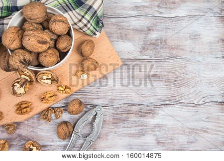 Walnuts, Nutcracker And Towel On Cutting Board. Top View.