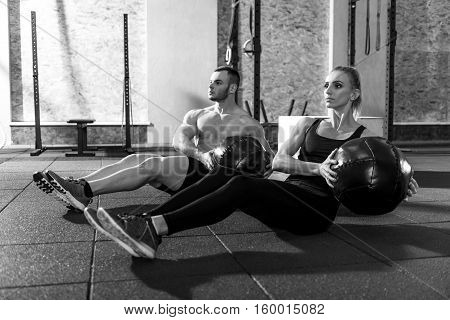 Synchronous moves. Pleasant good looking workout partners sitting on the floor and holding med balls while working out together