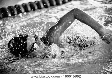 Female swimming in swimming lanes, black and white