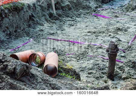 A uncovered pipeline construction site with sand around it for making pipeline for heating system. Three short red pipes in the earthen trench for making the pipeline.