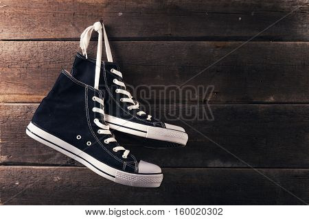 pair of sneakers hang on a nail on a old wooden plank background