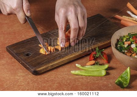 Chef chopping vegetables on kitchen board. Choped vegetables