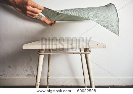 Man's hands raise a large green and white checkered napkin over an old toy table painted in white with little rust stains against white wall background.