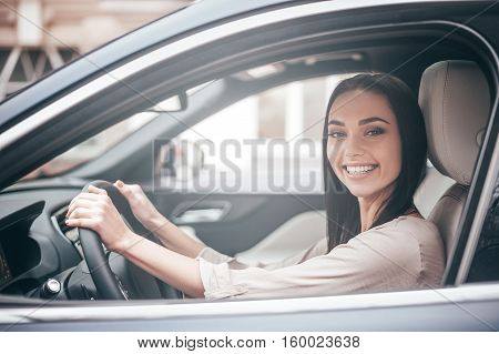 On the way to success. Confident young woman sitting on the front seat and smiling while driving a car