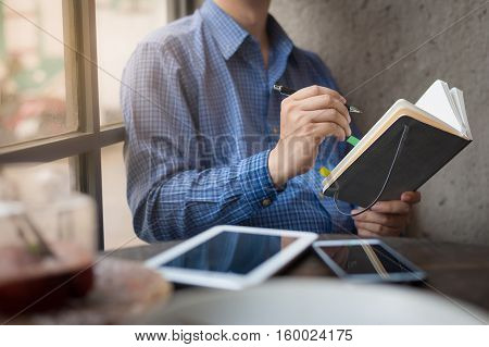 Adult freelance businessman writing on small notebook in cafe on weekend morning. Freelance business lifestyle concept