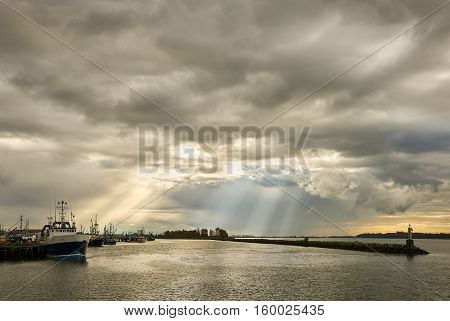 Steveston Storm Clouds and Sun Beams. Cracks in the storm over Steveston Harbour in the morning. British Columbia, Canada.
