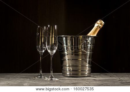 bottle of champagne and two glasses over dark background