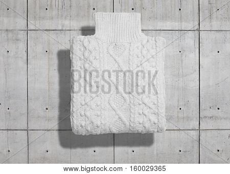 Turtleneck cotton cableknit white warm sweater neatly folded isolated on industrial concrete background