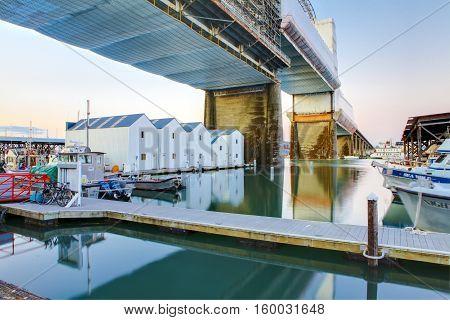 Tacoma Downtown Marina With Boat Houses Under Large Bridge.