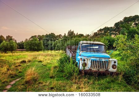 Old lorry in the field before sunset