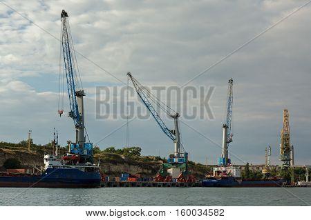 Sevastopol, Russia - June 09, 2016: Floating cranes lift trucks in the Bay of Black Sea.