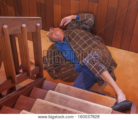 A senior man trying to get up after falling down the stairs