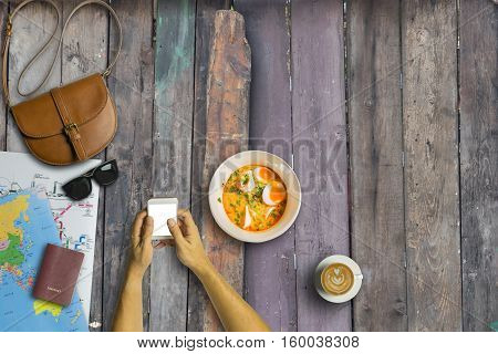 Concept Of Hipster Travel Traveler Shopping And Eating Tom Yum Kung Noodle Ramen. Hand Using Smartph