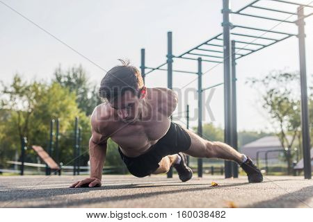 Athlete young man doing one-arm push-up exercise working out his upper body muscles outside in summer